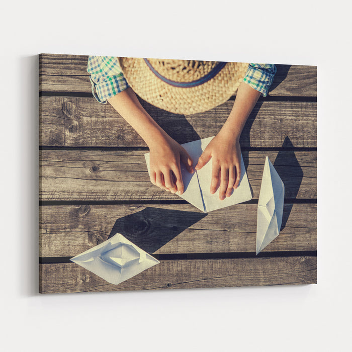 Boy Hands Making A Paper Boats On The Pier Top View Canvas Wall Art Print