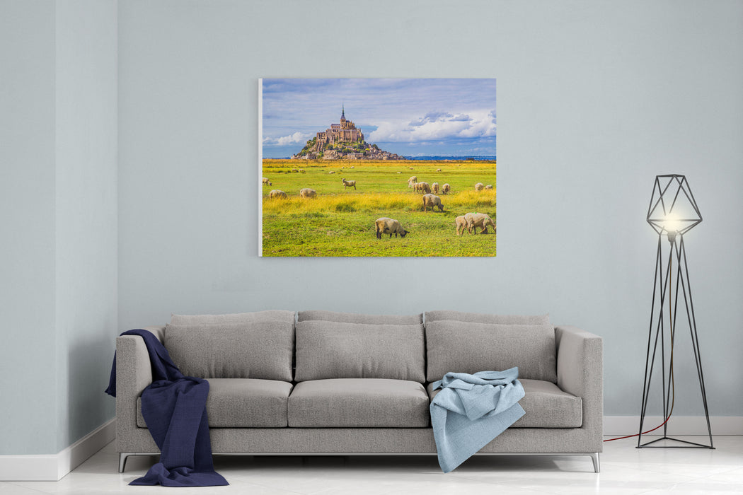Beautiful View Of Famous Historic Le Mont SaintMichel Tidal Island With Sheep Grazing On Fields Of Fresh Green Grass On A Sunny Day With Blue Sky And Clouds In Summer, Normandy, Northern France Canvas Wall Art Print
