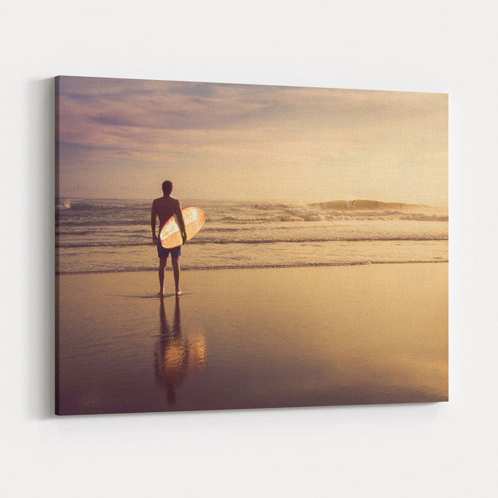 A Man Is Standing With A Surf In His Hands On The Sea Shore Canvas Wall Art Print