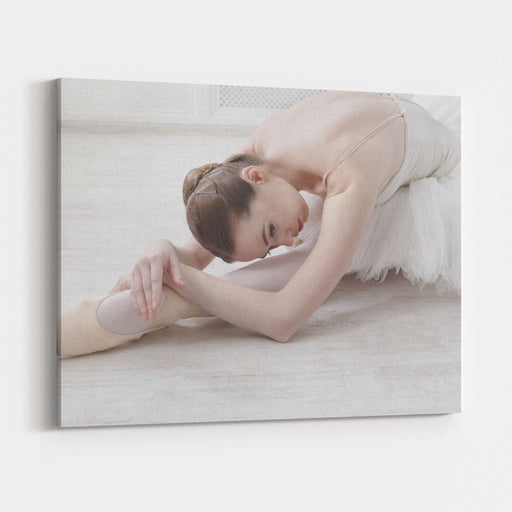 Beautiful Graceful Young Ballerina In Pointe Shoes At White Wooden Floor Makes Ballet Leg Stretching Ballet Practice Of Classical Dancer Canvas Wall Art Print
