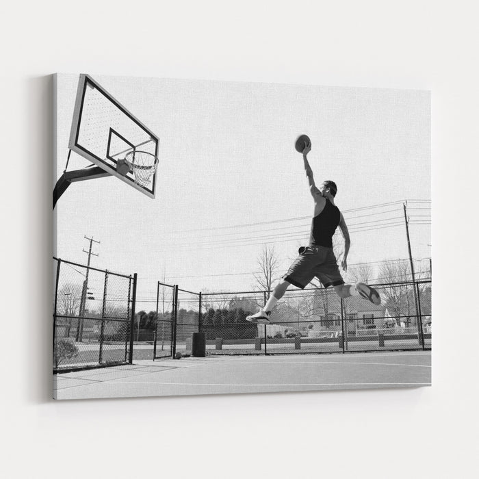 A Young Basketball Player Flying Towards The Rim For A Slam Dunk Canvas Wall Art Print