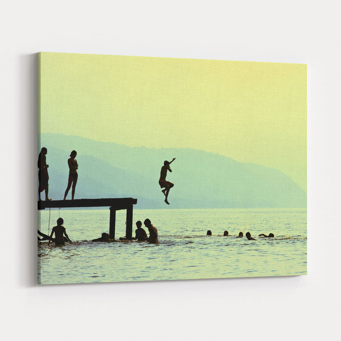 Silhouettes Of Kids Who Jump Off Dock On The Lake At Sunset Canvas Wall Art Print