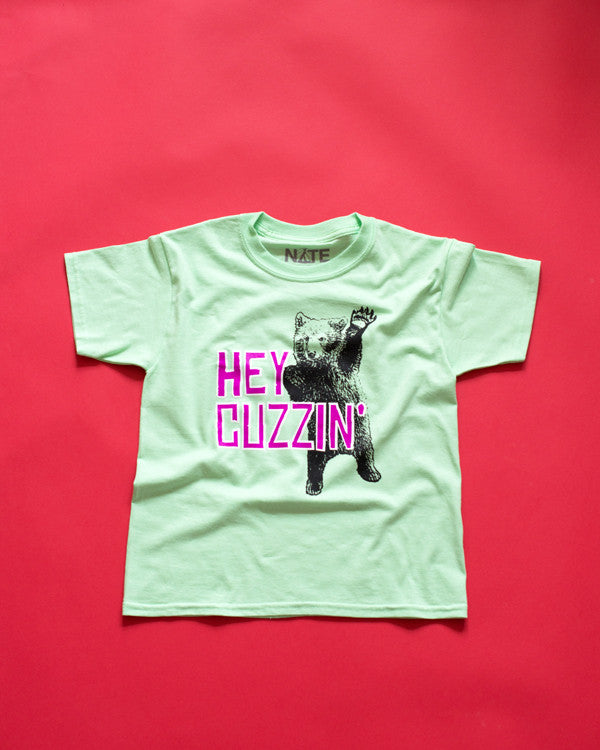 Youth t-shirt with cute waving bear, purple, white and black design on a bright mint T-Shirt.