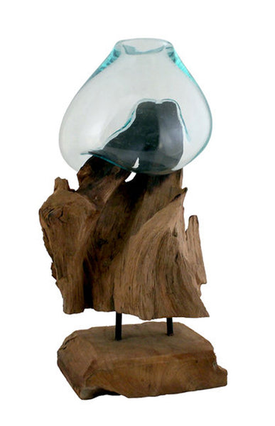 "This 12"" tall handblown glass and teak wood sculpture has been handcrafted by skilled artisans who have a love for the art of glass blowing. Recycled glass is blown onto the shape of the teak wood root and begins to flow and cradling the form of the wood to create a bowl that is a unique, one of a kind, piece that can be used as a vase, terrarium or fishbowl."