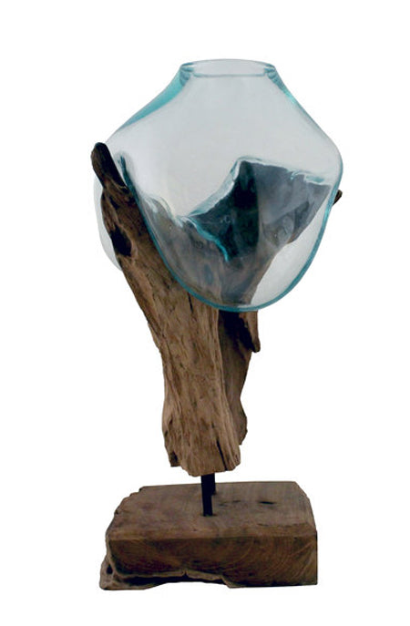 "This 18"" tall handblown glass and teak wood sculpture has been handcrafted by skilled artisans who have a love for the art of glass blowing. Recycled glass is blown onto the shape of the teak wood root and begins to flow and cradling the form of the wood to create a bowl that is a unique, one of a kind, piece that can be used as a vase, terrarium or fishbowl."