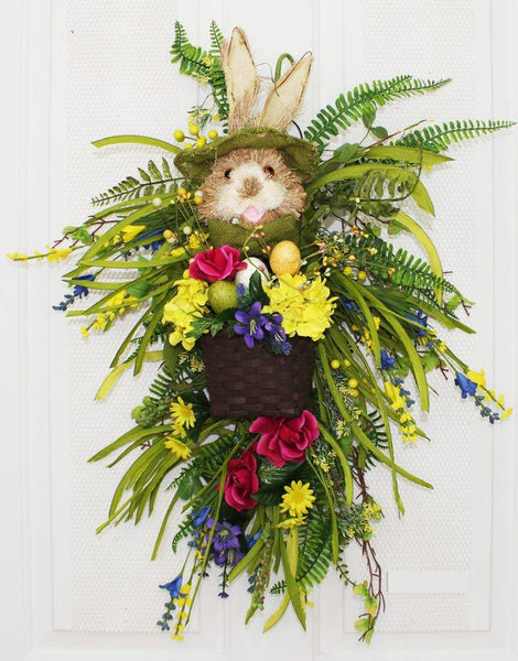 "Our Bowtie Bunny With Basket Easter Spring Teardrop Front Door Wreath is 23"" in length and features colorful silk flowers as well as a festive bunny rabbit all dressed up with green brim hat and matching bowtie and holding a basket full of flowers and Easter eggs and surrounded with lots of wispy greens and ferns"