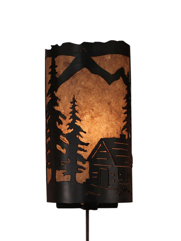 Our Rustic Cabin Panel Wall Sconce captures the forested beauty with cutouts of a metal cabin and trees in front of the amber parchment paper shade