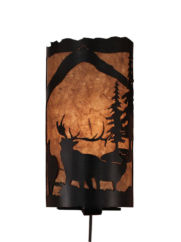 Our Rustic Elk Panel Wall Sconce captures the forested beauty of cutouts of metal elk and trees in front of the amber parchment paper shade