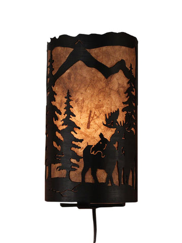 Our Rustic Moose Panel Wall Sconce captures the forested beauty with cutouts of metal moose and trees in front of the amber parchment paper shade