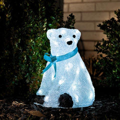 Konstsmide acrylic polar bear with blue ribbon standing in garden border