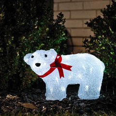 Konstsmide acrylic polar bear with red ribbon standing in garden border