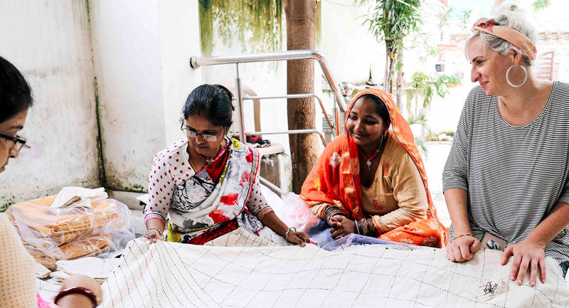 Anchal artisans quality controlling a piece hand stitched by a woman in Ajmer, India