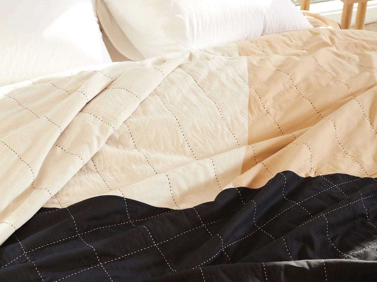 Close up view of Anchal x Brooklinen bedding in tan, black and cream
