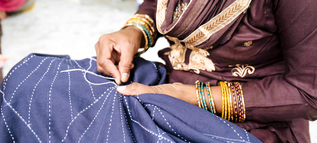 Artisan hand stitching fabric for the Anchal Array cocoon jacket