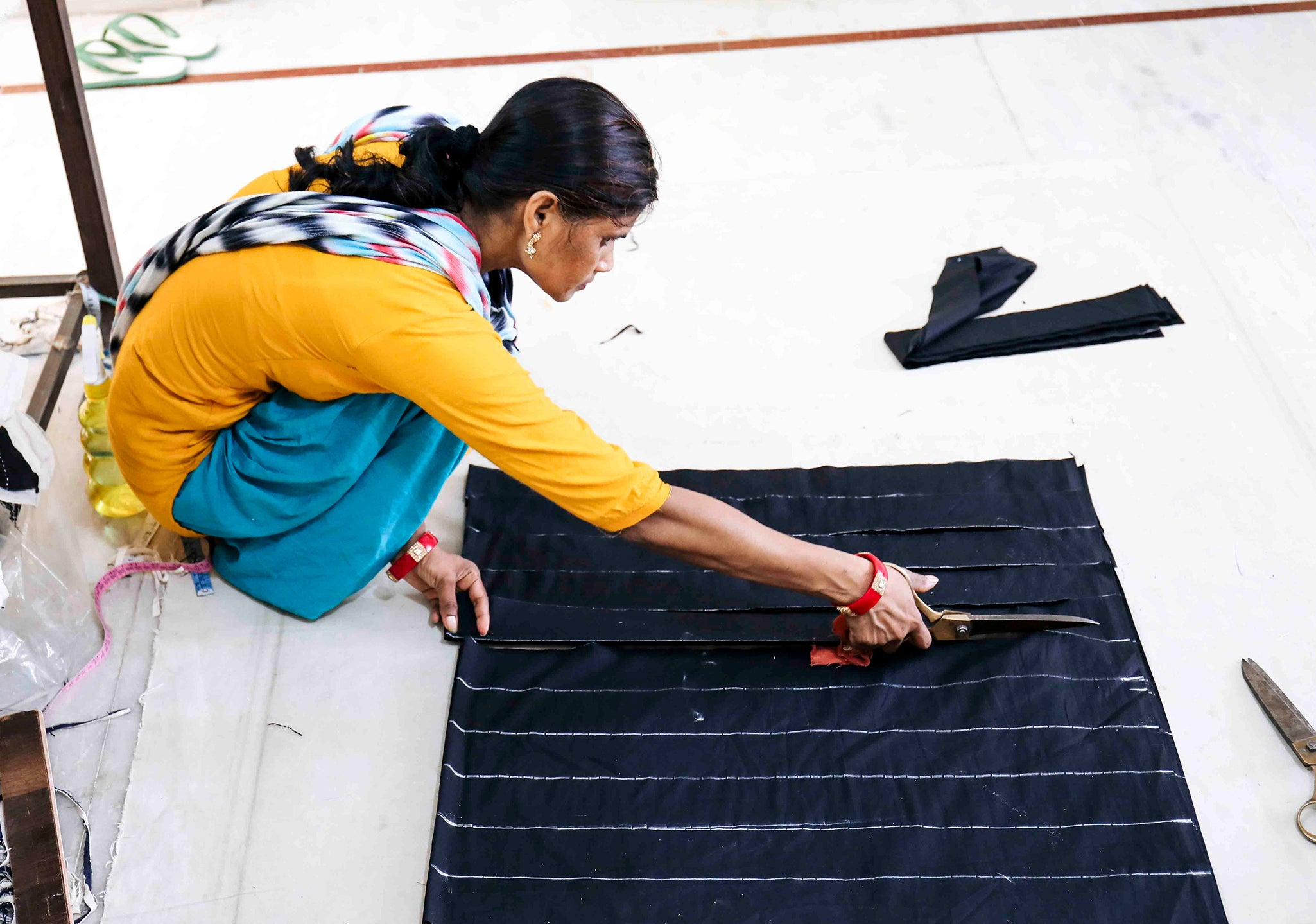 Anchal artisan cutting patchwork pieces for Fall/Winter collection