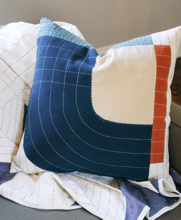 modern decorative throw pillow with navy and rust geometric design