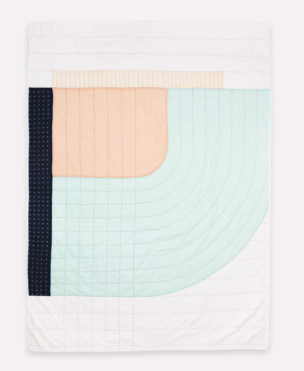 Organic cotton throw quilt with pastel-toned colors and curve design made by anchal artisans