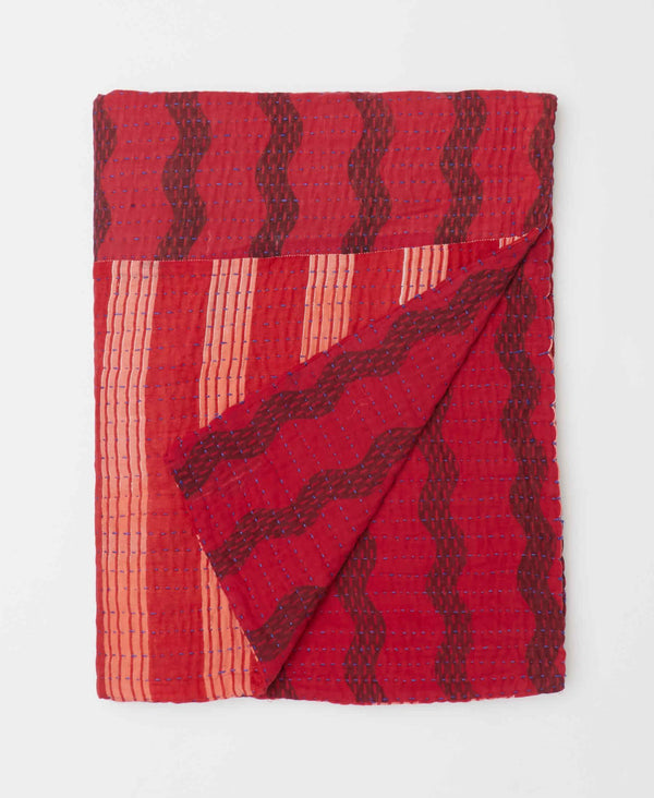 Bold red colors throughout this small Kantha quilt throw which features a wavy design