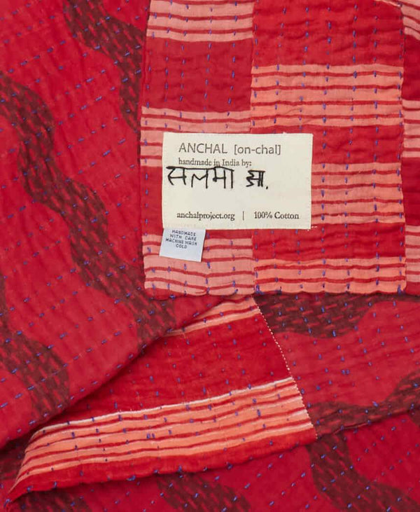 Different shades of red contrasted by blue Kantha stitching throughout this soft cotton quilt