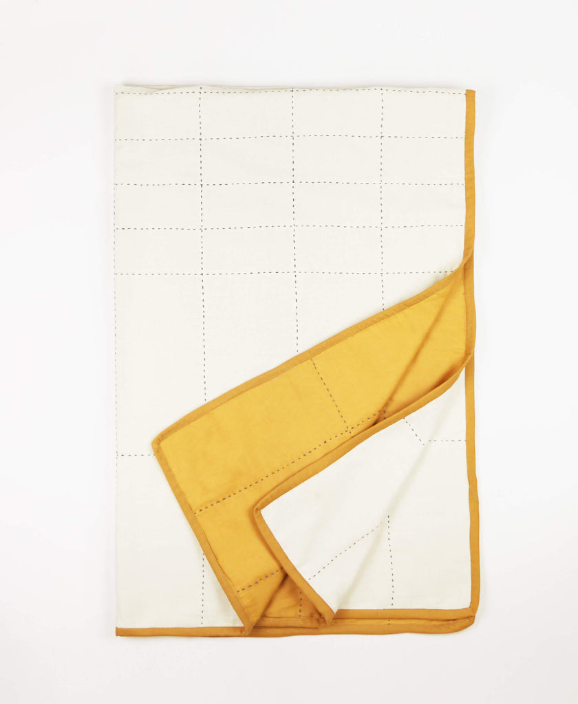 Small mustard-colored organic cotton throw quilt with grid-stitched pattern