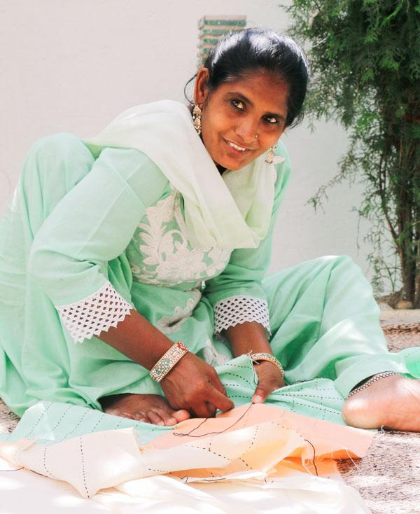 Anchal Project artisan Madina hand stitching a patchwork pillow