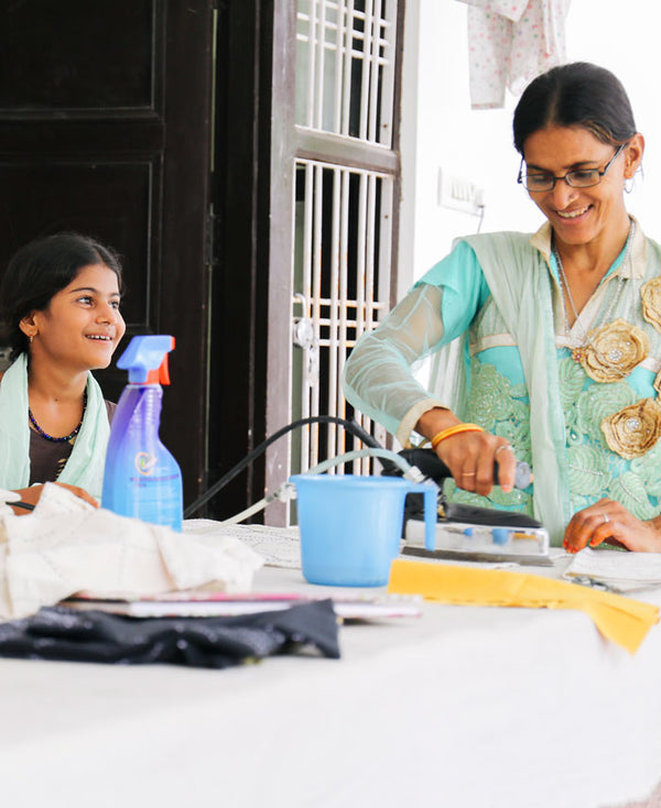 Anchal Project artisan using a steam iron in the Anchal workshop