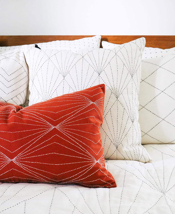 all white modern organic cotton bedding with geometric throw pillow arrangement