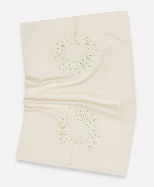 Wrinkled light ivory kitchen towel with a Chamaerops leaf in green stitching