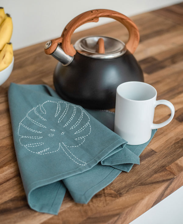hand-embroidered organic cotton tea towel with plant design