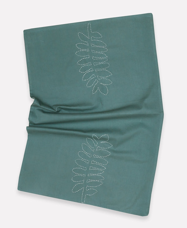 Wrinkled blue/green tea towel featuring a leaf design with white stitching made from artisans in Ajmer, India