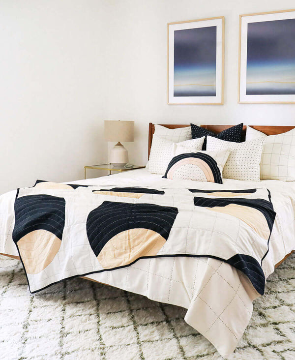 modern kantha quilt with circular lunar design on black and white bed