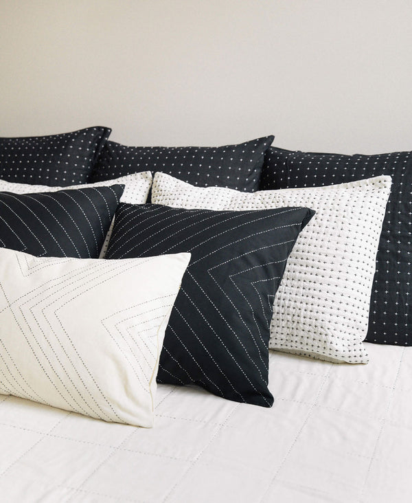 luxury organic cotton black and white pillow arrangement with detailed embroidery