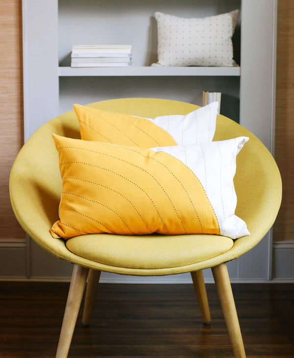 Anchal Project organic cotton gold lumbar pillow in mid-century modern chair