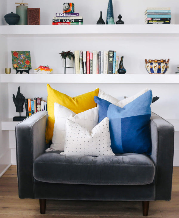 bright modern pillow arrangement in velvet gray chair