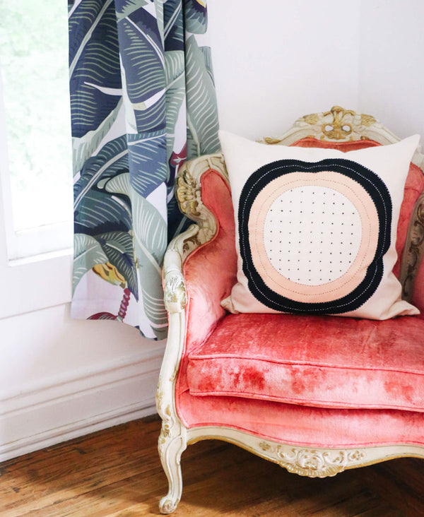 modern fair trade throw pillow in vintage pink velvet chair