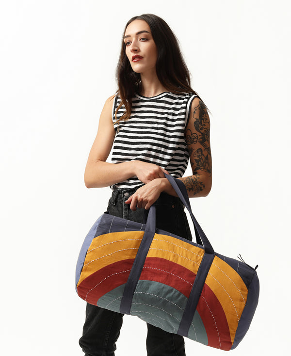 Bright colored weekender bag with curve design and white traditional stitching