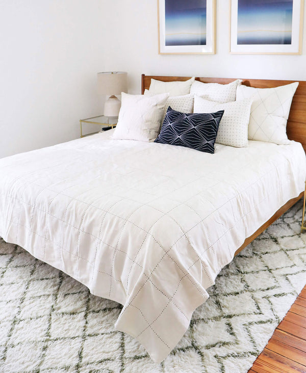 Eco-friendly quilt bedding styled in a modern bedroom paired with handmade organic cotton pillows