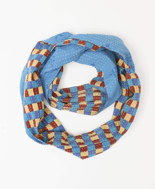 Blue, red, and cream checkerboard infinity scarf reversible with a minimalist blue design hand-stitched by Anchal artisans
