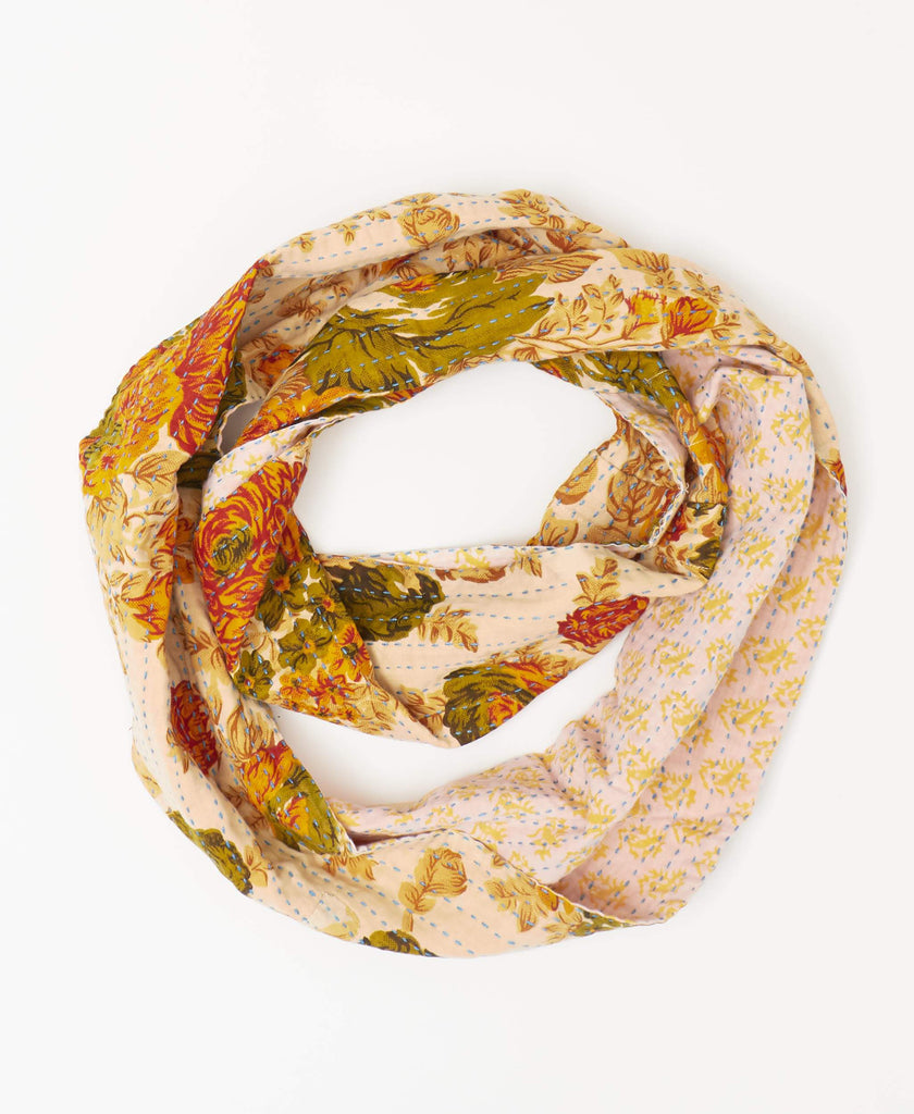 Pink reversible infinity kantha scarf with bright orange patterning on one side and deep red, orange and green floral patterns on the revers