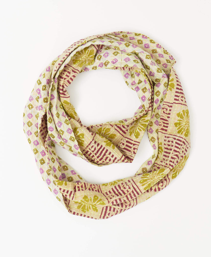 Anchal cream reversible Kantha infinity scarf with green floral and red stripe patterning on one side and a small green and purple geometric pattern on the reverse