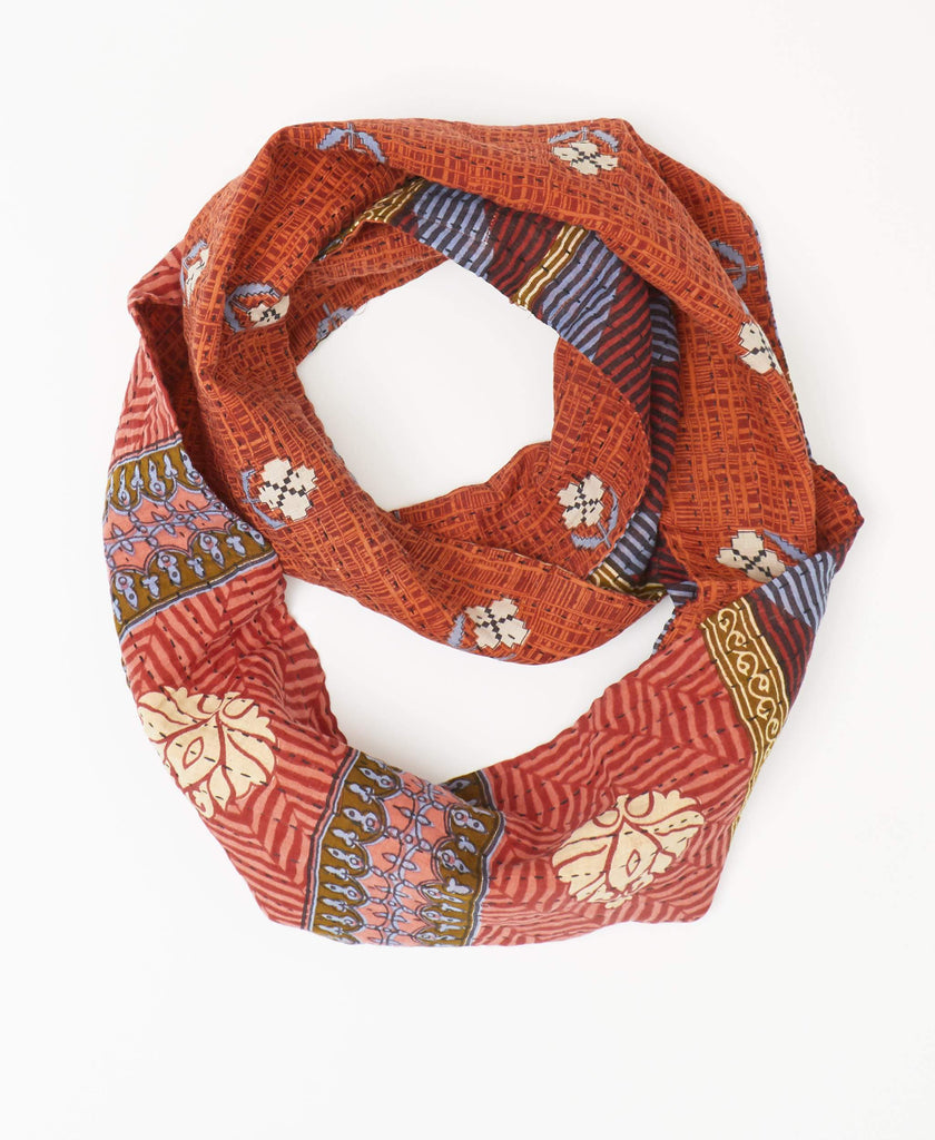 Orange Kantha infinity scarf with a white floral pattern and blue and red stripe pattern on the reverse