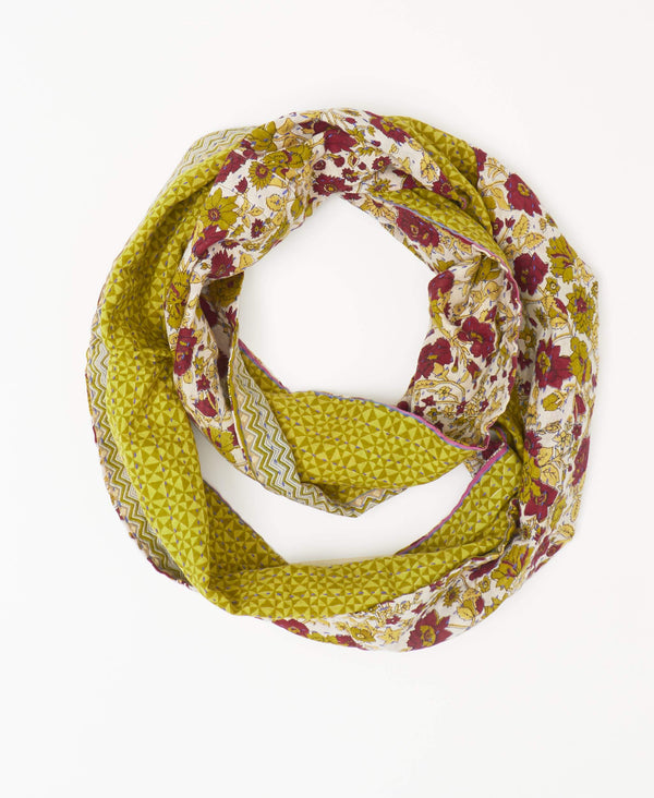 Ethically made green and dark red reversible infinity scarf with a floral pattern on one side and a geometric on the reverse