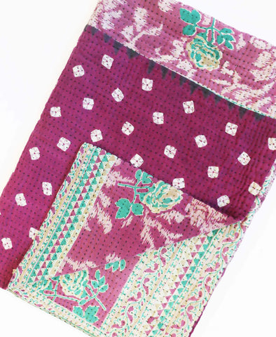 Purple vintage cotton quilt with mint floral and green stripe pattern with a black kantha stitch