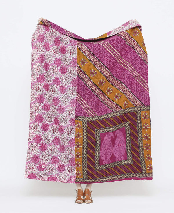 Purple and orange vintage throw quilt with white detailing and floral and paisley patterns with black kantha stitching