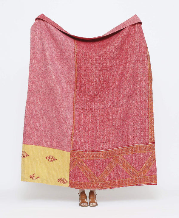 Pink vintage throw quilt with yellow detailing and floral and zig-zag patterns with white kantha stitching