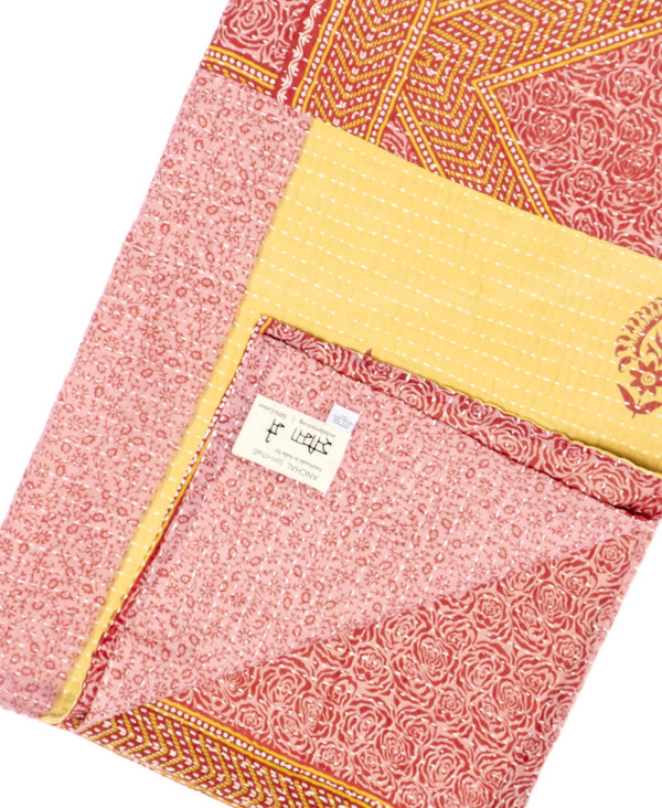 Fair trade pink throw quilt handstitched by Anchal artisans in Ajmer India with tiny floral and paisley designs