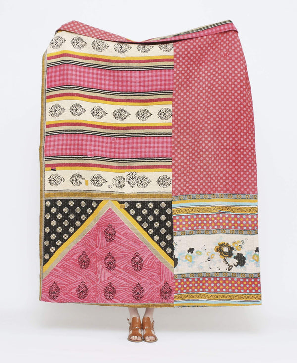 Pink and white vintage throw quilt with yellow and light blue detailing and floral, striped, and polka dot patterns with white kantha stitching