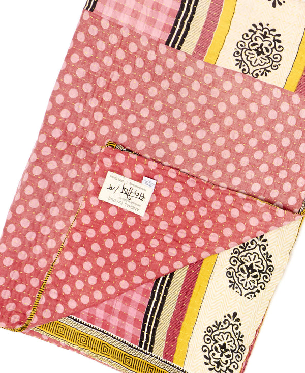 Fair trade pink and white throw quilt handmade by Anchal artisans in Ajmer India with striped, floral, polka dot, and paisley designs