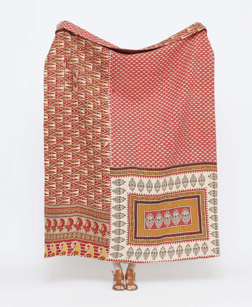 Red vintage throw quilt with yellow and white detailing and paisley patterns and geometric shapes with white kantha stitching