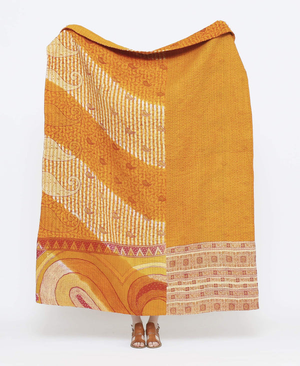 Orange vintage throw quilt with red detailing and large paisley and striped prints with purple kantha stitching